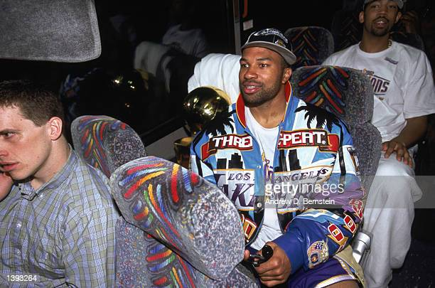 Point guard Derek Fisher of the Los Angeles Lakers sits with the championship trophy on the team bus after winning Game Four of the 2002 NBA Finals...