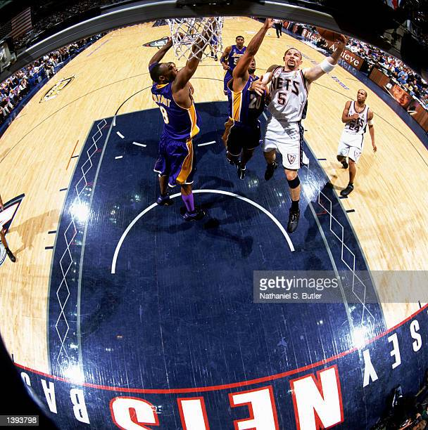 Point guard Jason Kidd of the New Jersey Nets shoots around guards Kobe Bryant ad Brian Shaw of the Los Angeles Lakers during Game Four of the 2002...