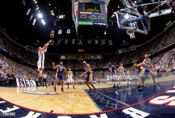 Point guard Jason Kidd of the New Jersey Nets shoots over point guard Derek Fisher and forward Robert Horry of the Los Angeles Lakers during Game...