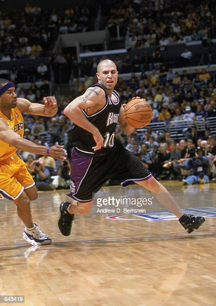Point guard Mike Bibby of the Sacramento Kings drives the ball to the paint around guard Derek Fisher of the Los Angeles Lakers in game 3 of the 2002...