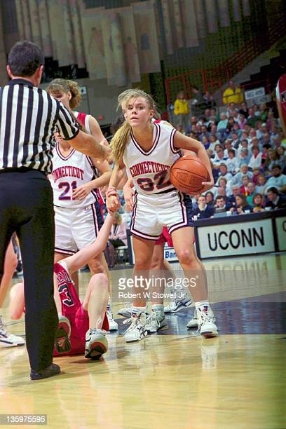 Point guard Pam Weber of the University of Connecticut helps an opponent off the floor as she waits for a call by the referee Storrs CT 1995