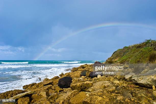 A rainbow rises out of the ocean near a boulder-strewn shoreline.