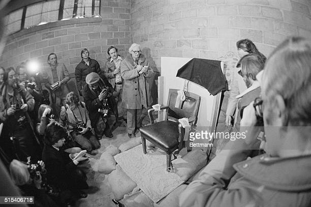 Photo of a group of newsmen looking at and taking photos of the chair in which Gary Gilmore sat when facing the firing squad here 1/17 Draped over...