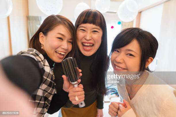 Point of view as three young women take a selfie whilst singing Karaoke at home using a hair brush at Christmas
