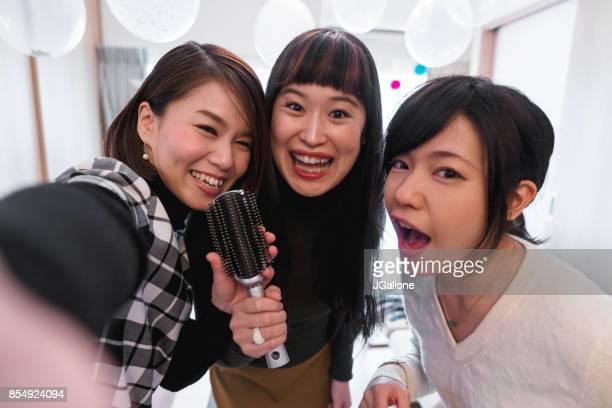 Selfie 家でカラオケを歌いながら、3 人の若い女性としての視点がクリスマスにヘアブラシを使用してください。