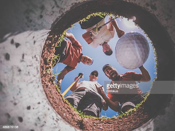 Point Of View Golf Players and Ball From Inside Hole