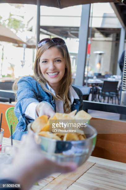 point of view of being offered a bowl of chips across a table - texas bowl stock photos and pictures