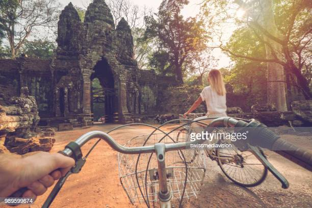 Point of view of couple cycling in temple complex in Asia at sunset