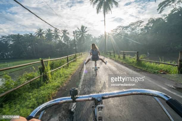 Point of view of couple cycling near rice fields at sunrise, Asia
