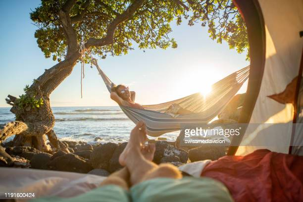 point of view of man's feet from inside a tent camping on the beach in hawaii looking at girlfriend in hammock outdoors - hawaii islands stock pictures, royalty-free photos & images