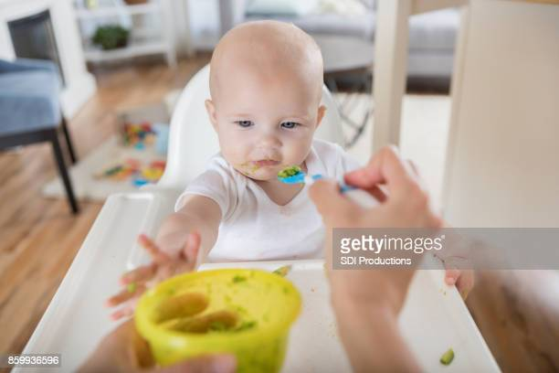 point of view of mom feeding her baby with a spoon - point of view stock pictures, royalty-free photos & images
