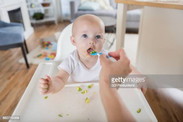 Point of view of mother spoon feeding hungry baby