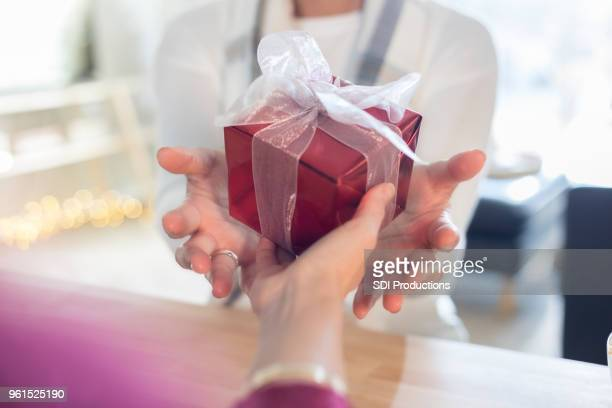 Point of view of someone who is giving gift to unrecognizable woman