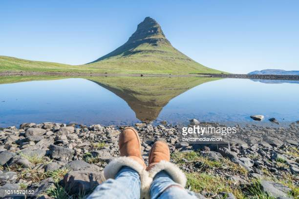 point of view of woman's feet at kirkjufell mountain in iceland - reflection lake stock photos and pictures