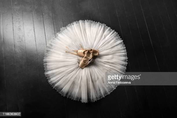 pointe shoes. peach shoes, ballet shoes with ribbons on a white tutu in a dance studio. advertising ballet school. professional ballerina outfit. - satin dress stock pictures, royalty-free photos & images