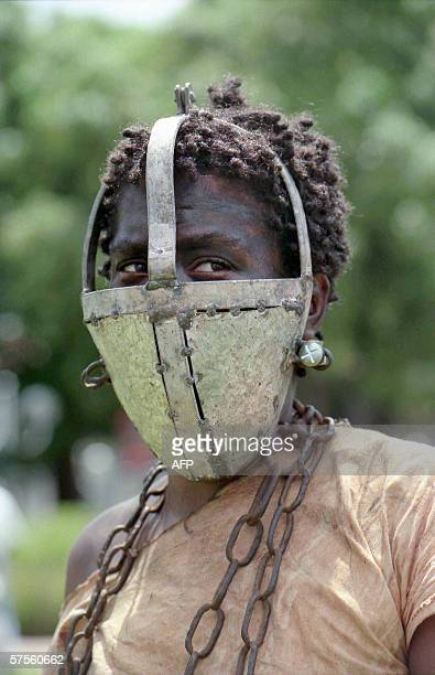 A picture taken 27 May 1998 shows an actress wearing a mask supposed to prevent her from eating sugar cane taking part in the reenactment of slaves...