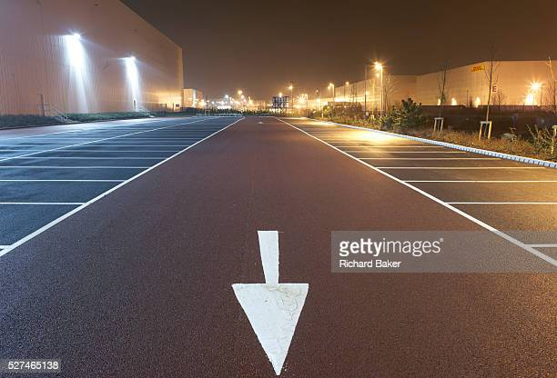 Pointing towards the viewer and the bottom of the picture near empty parking bay markings a stencilled arrow directs traffic flow at the DIRFT...