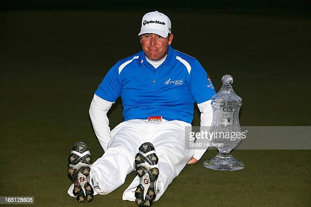 """Points strikes a """"Dufnering"""" pose with the trophy on the 18th green after winning the Shell Houston Open at the Redstone Golf Club on March 31, 2013..."""