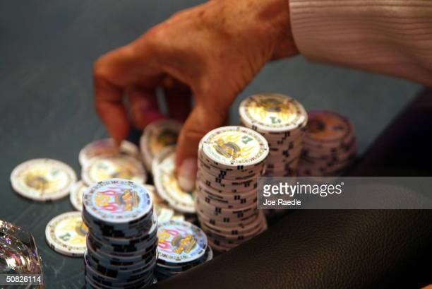 A poker player prepares to throw her chips on the table May 11 2004 during the grand opening for the Seminole Hard Rock Hotel and Casino in Hollywood...