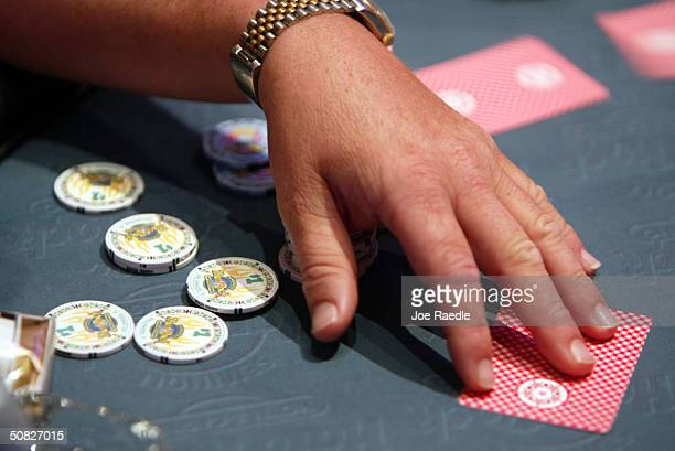 A poker player takes his cards May 11 2004 during the grand opening for the Seminole Hard Rock Hotel and Casino in Hollywood Florida South Florida's...