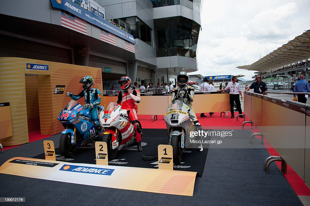 Pol Espargaro of Spain and HP Tuenti Speed Up, Stefan Bradl of Germany and Viessmann Kiefer Racing and Thomas Luthi of Switzerland and Interwetten Paddock wait the mechanics on the bike under the podium after the forced end of at the end of the Moto2 race of MotoGP of Malaysia at Sepang Circuit on October 23, 2011 in Kuala Lumpur, Malaysia.