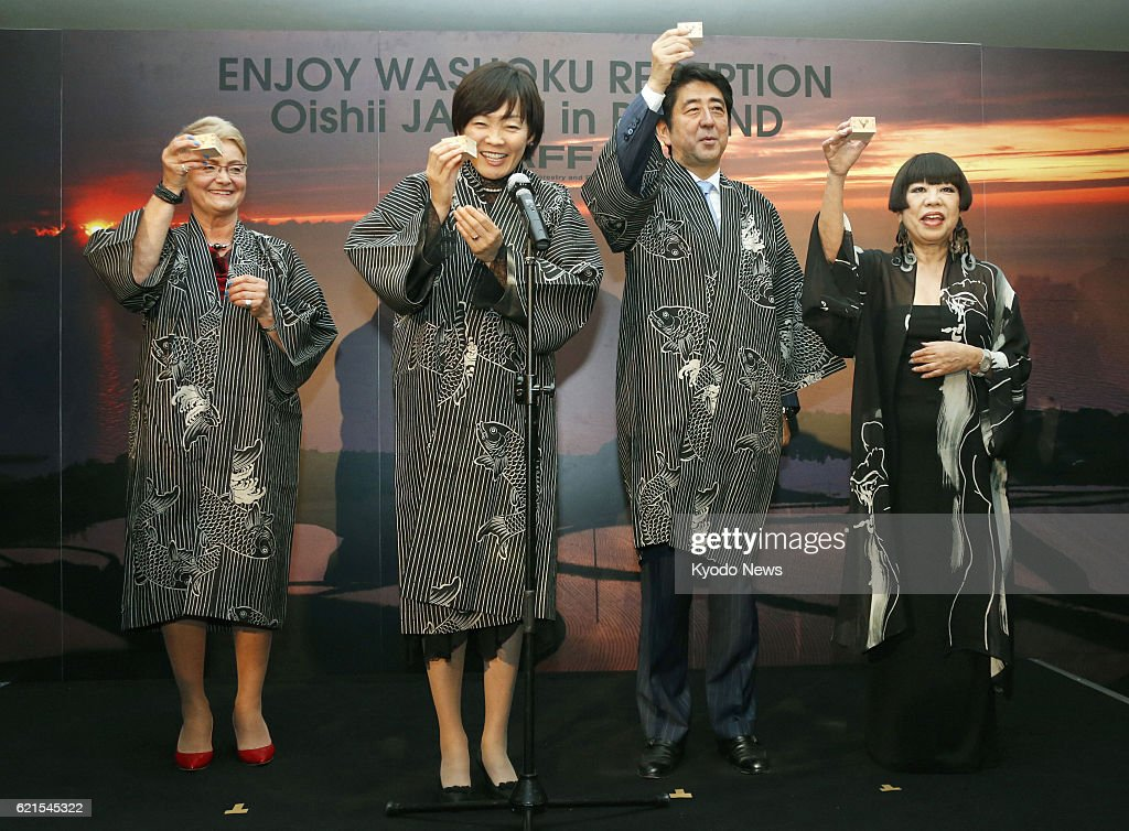 WARSAW, Poland - Japanese Prime Minister Shinzo Abe (2nd from R) and his wife Akie (2nd from L) make a toast at a reception to introduce Japanese food culture in Warsaw, Poland, on June 15, 2013. On the right is Japanese fashion designer Junko Koshino.