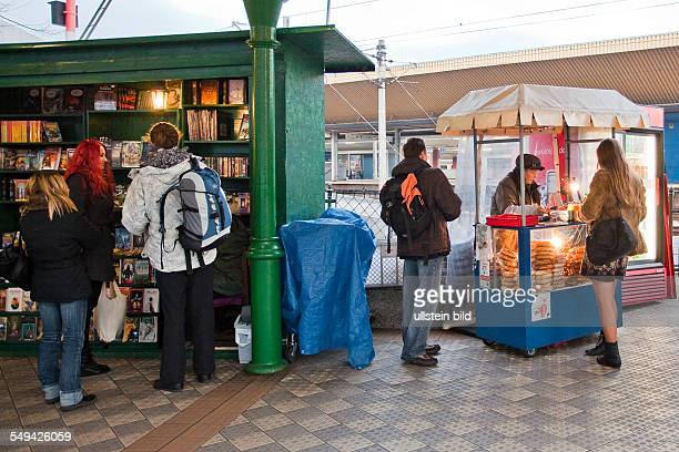 woman selling famous pretzel besides an openairbookstore near the central station