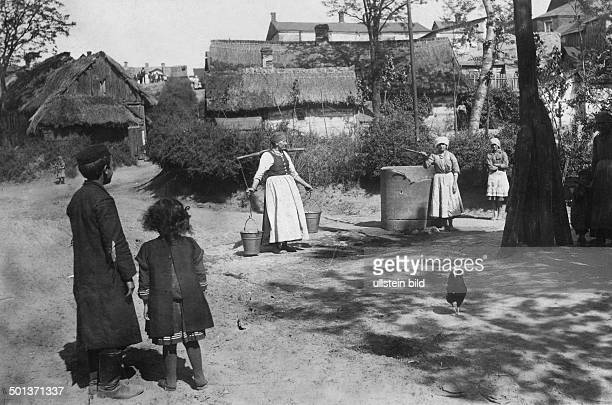 residents of a village get water from a well probably in the 1910s