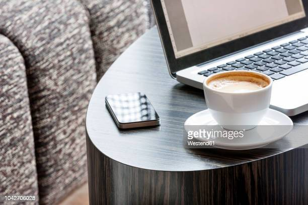 poland, warsaw, laptop, smartphone and coffee cup at lounge of hotel - coffee table stock pictures, royalty-free photos & images