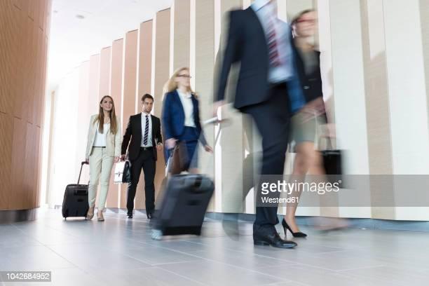 poland, warzawa, group of businessmen arriving at hotel - kleine personengruppe stock-fotos und bilder