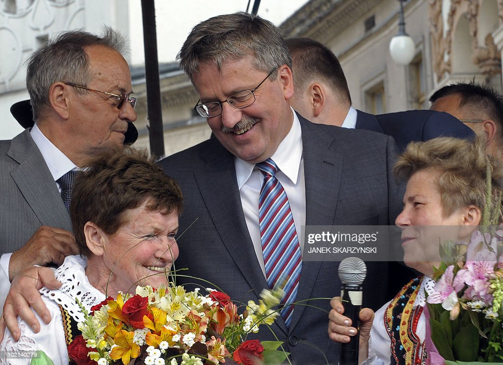 Poland's acting president Bronislaw Komorowski talks with flower sellers from Krakow's market square during his electorial rally on June 16,2010 in Krakow. Liberal candidate Komorowski scored a 14 percentage point lead on his conservative rival Jaroslaw Kaczynski in poll published today, four days ahead of Poland's snap presidential poll Sunday.