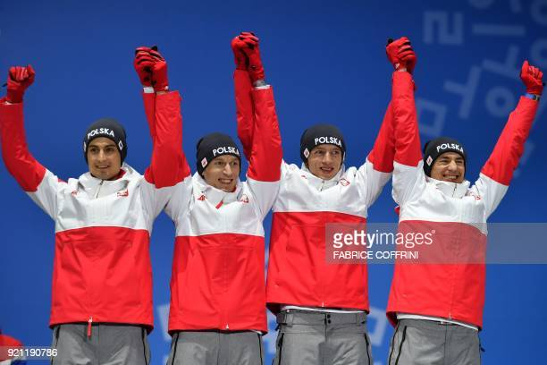 Poland's bronze medallists Stefan Hula Maciej Kot Dawid Kubacki and Kamil Stoch pose on the podium during the medal ceremony for the men's team ski...