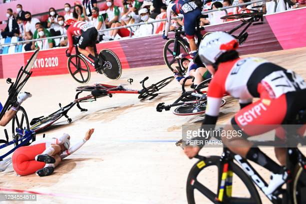 Poland's Daria Pikulik and Britain's Laura Kenny crash while competing in the women's track cycling omnium scratch race during the Tokyo 2020 Olympic...