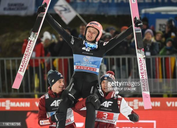 Poland's Dawid Kubacki is lifted by Poland's Piotr Zyla and Poland's Kamil Stoch after winning the fourth stage of the Four Hills Ski Jumping...