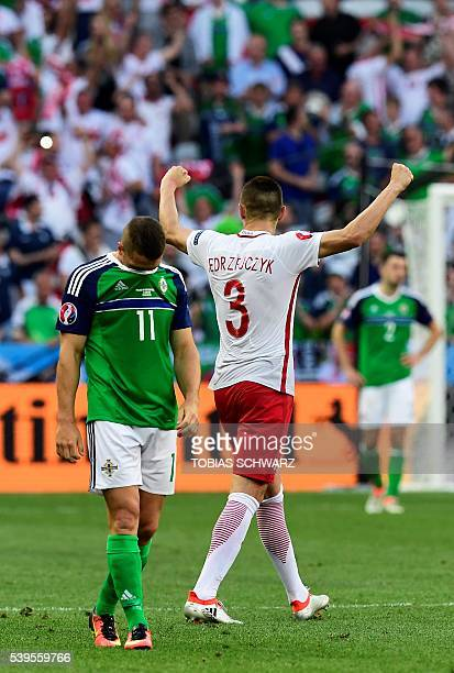 Poland's defender Artur Jedrzejczyk celebrates his team's victory next to Northern Ireland's forward Conor Washington at the end of the Euro 2016...
