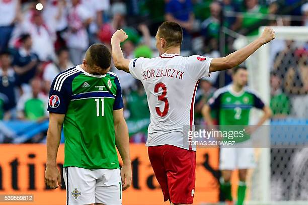 TOPSHOT Poland's defender Artur Jedrzejczyk celebrates his team's victory next to Northern Ireland's forward Conor Washington at the end of the Euro...