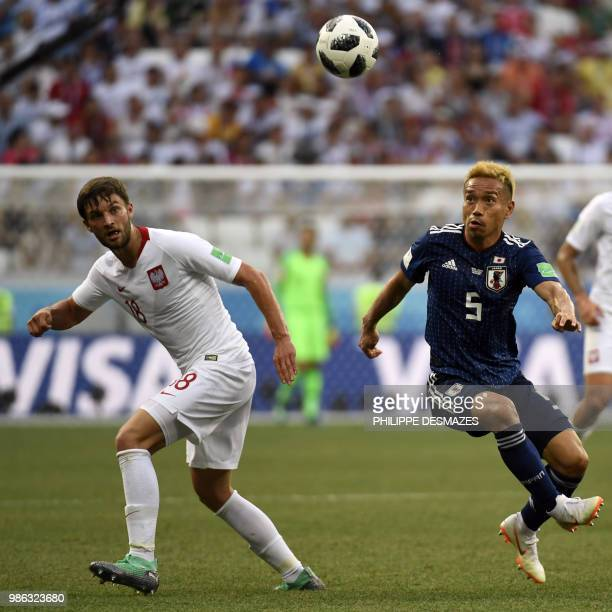 Poland's defender Bartosz Bereszynski and Japan's defender Yuto Nagatomo eye the ball during the Russia 2018 World Cup Group H football match between...
