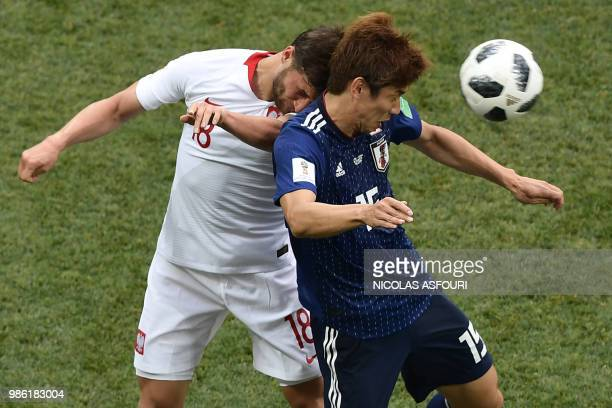 TOPSHOT Poland's defender Bartosz Bereszynski challenges Japan's forward Yuya Osako during the Russia 2018 World Cup Group H football match between...