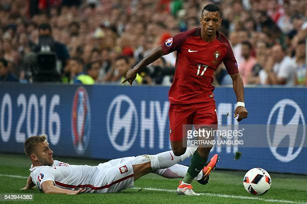 Poland's defender Jakub Wawrzyniak falls next to Portugal's forward Nani during the Euro 2016 quarterfinal football match between Poland and Portugal...