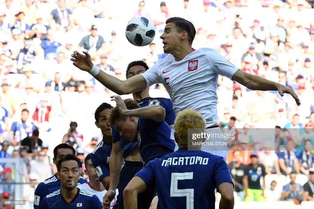 TOPSHOT - Poland's defender Jan Bednarek (top) heads the ball during the Russia 2018 World Cup Group H football match between Japan and Poland at the Volgograd Arena in Volgograd on June 28, 2018. (Photo by Mark RALSTON / AFP) / RESTRICTED