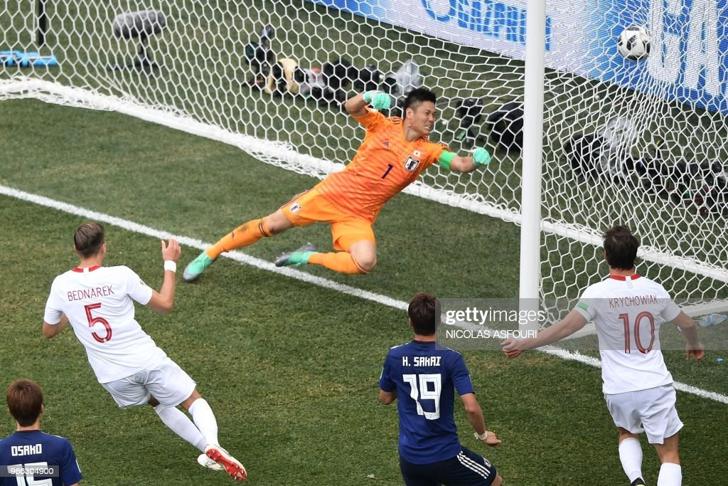 TOPSHOT - Poland's defender Jan Bednarek (L) scores the opening goal past Japan's goalkeeper Eiji Kawashima (top) during the Russia 2018 World Cup Group H football match between Japan and Poland at the Volgograd Arena in Volgograd on June 28, 2018. (Photo by NICOLAS ASFOURI / AFP) / RESTRICTED
