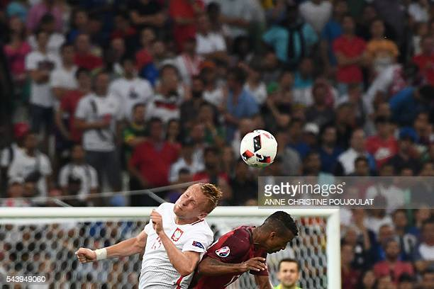 Poland's defender Kamil Glik jumps for the ball Portugal's forward Nani during the Euro 2016 quarterfinal football match between Poland and Portugal...
