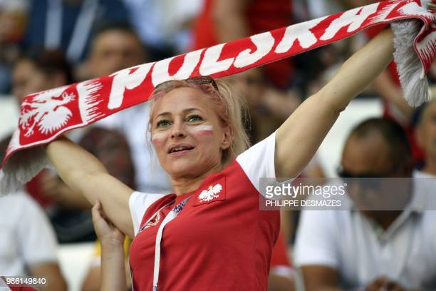 A Poland's fan brandishes her scarf before the Russia 2018 World Cup Group H football match between Japan and Poland at the Volgograd Arena in...
