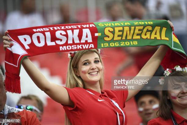 A Poland's fan poses with a scarf for Polish and Senegalese teams as she cheers prior to the Russia 2018 World Cup Group H football match between...