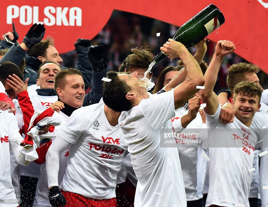 Poland's forward and captain Robert Lewandowski (C) drinks champagne as teammates celebrate the qualification with jersey reading 'Vive la Pologne 2016 ' after the Euro 2016 Group D qualifying football match between Poland and the Republic of Ireland at the Stadion Narodowy in Warsaw on October 11, 2015.