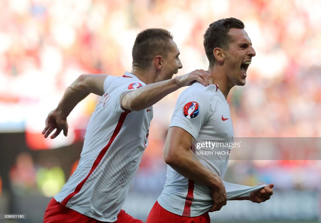 TOPSHOT - Poland's forward Arkadiusz Milik (R) celebrates his goal with Poland's defender Artur Jedrzejczyk during the Euro 2016 group C football match between Poland and Northern Ireland at the Allianz Riviera stadium in Nice on June 12, 2016. / AFP PHOTO / Valery HACHE