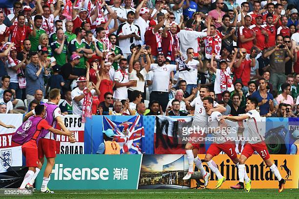 Poland's forward Arkadiusz Milik is congratulated by teammates after scoring a goal during the Euro 2016 group C football match between Poland and...