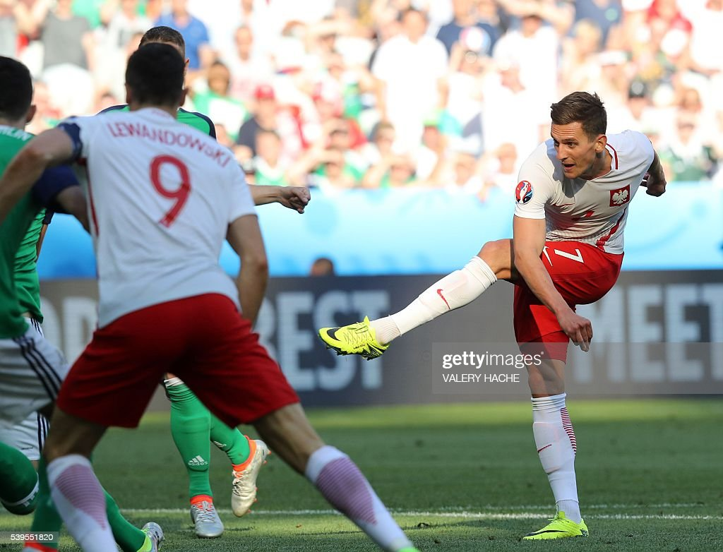 Poland's forward Arkadiusz Milik (R) shoots to score during the Euro 2016 group C football match between Poland and Northern Ireland at the Allianz Riviera stadium in Nice on June 12, 2016. / AFP / Valery HACHE