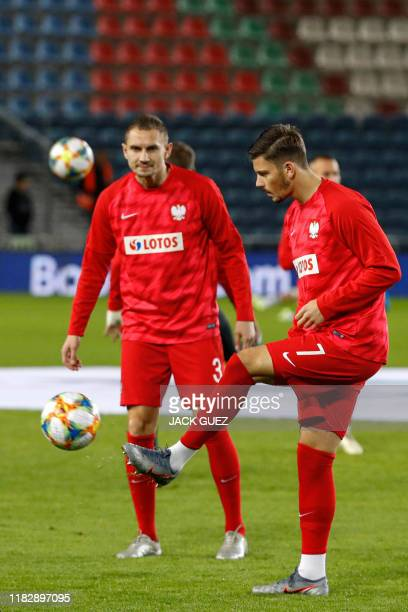 Poland's forward Dawid Kownacki and defender Artur Jedrzejczyk warm up on the pitch ahead of the EURO 2020 group G qualifiers football match between...