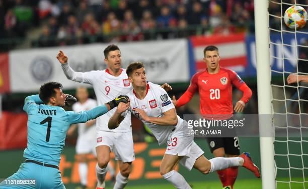 Poland's forward Krzysztof Piatek scores the opening goal past Austria's goalkeeper Heinz Linder during the UEFA Euro 2020 Group B qualification...